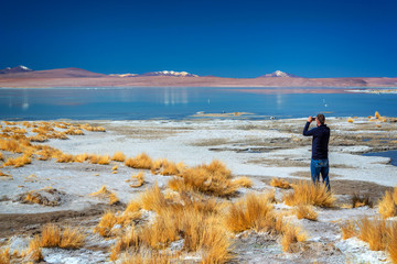 Man taking picture of Laguna Polques, Sud Lipez province, Potosi, Bolivia