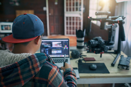Young freelancer man editing video on laptop for uploading video to internet online or social media.