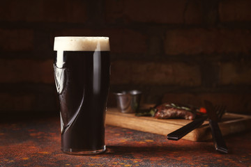 Obraz Glass of cold dark beer on color table - fototapety do salonu