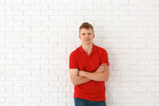 Portrait of handsome young man against white brick wall