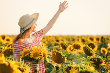 Beautiful redhead woman in sunflower field on sunny day Fototapete