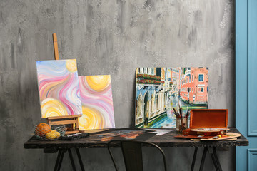 Beautiful pictures with brushes and paints on table in artist's workshop