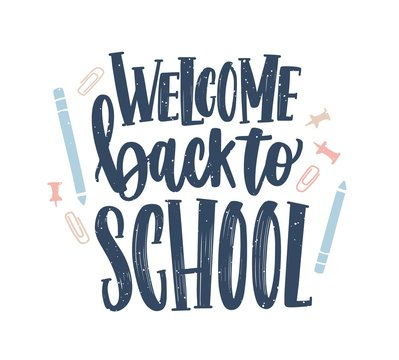 Welcome Back to School lettering handwritten with elegant calligraphic font and decorated by paper clips, push pins and pencils scattered around. Colorful vector illustration for 1st of September.