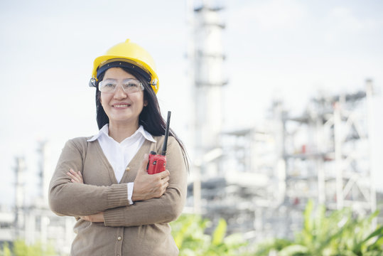 Woman Engineer and safety Officer concept.Young woman engineer wear safety hat (helmet),safety glasses and holding portable radio.Construction Safety Officer  inspector in front of refinery plant back