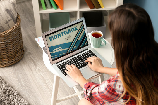 Woman using laptop to pay mortgage loan online at home