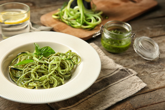 Plate of spaghetti with zucchini and pesto sauce on wooden table