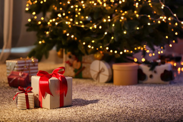 Fotobehang Bomen Beautiful Christmas gift boxes on floor near fir tree in room