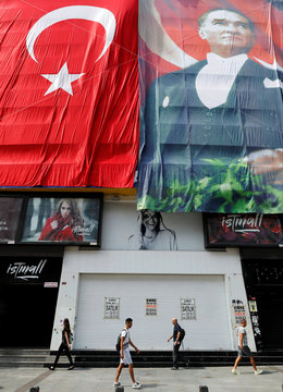 People walk in front of a building decorated with a giant Turkish flag and a poster of modern Turkey's founder Mustafa Kemal Ataturk in Istanbul
