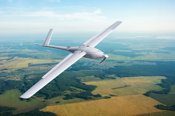 Unmanned military drone on patrol air territory at low altitude.