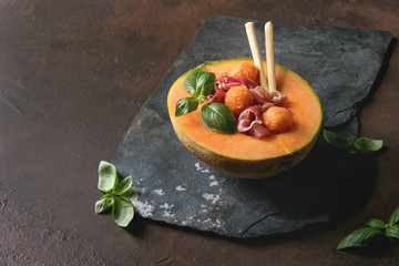 Melon and ham salad served in half of Cantaloupe melon with fresh basil and grissini bread on black slate board over dark brown texture background.