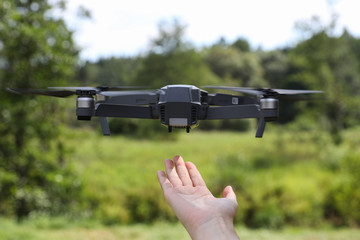 The girl catches the quadcopter outdoors after the flight