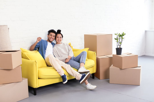 Happy interracial couple resting on sofa near carton boxes in room. Moving into new house