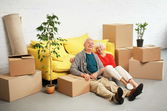 Mature couple sitting on floor near boxes and sofa after moving into new house