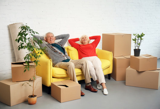 Mature couple sitting on sofa near boxes after moving into new house