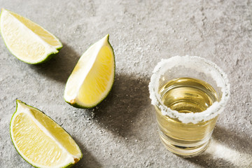 Mexican Gold tequila with lime and salt on gray background