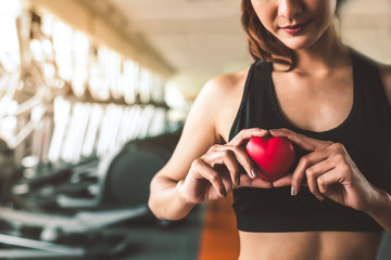 Happy sport woman holding red heart in fitness gym club. Medical cadio heart strength training lifestyle. Pretty female sport girl workout exercise. Cardiac healthy and wellbeing. Massage ball in hand