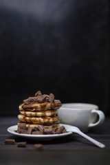 Freshly baked, tender punkeyki soaked in chocolate sauce with pieces of milk chocolate. With a Cup of coffee. On dark background.