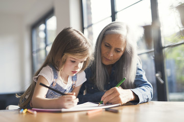 Grandmother and granddaughter making a drawing together