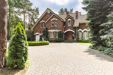 Large cobbled driveway in front of an impressive red brick English design mansion surrounded by old trees