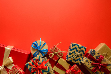 Top view on Christmas gifts wrapped in gift paper decorated with ribbon on red paper background. New Year, holidays and celebration decorations concept. Copy space. Flat lay