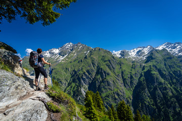 Female traveler with backpack hiking mountain trail and admiring views of Swiss Alps in Val de Bagnes area, Switzerland.