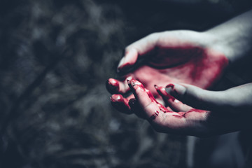 Close up of bloody hands in dark forest background. Horror and ghost concept. Criminal and murder concept. Halloween day and sacrifice theme. People and religion theme. Open the palm of the hands.