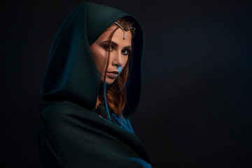Beatiful elf princess wearing dark green cape looking at camera from darkness.