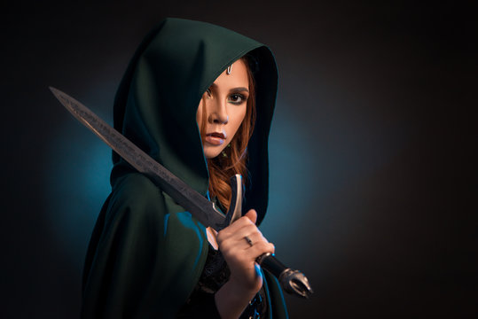 Mysterious young woman keeping sharp knife, wearing green cape with a hood.