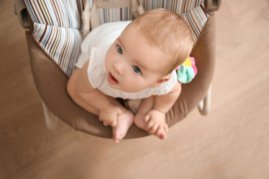 Cute baby in rocker looking at mother at home