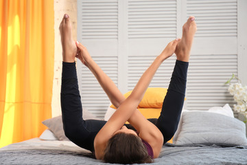 Sporty woman practicing yoga in bedroom
