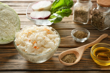 Bowl with delicious sauerkraut and spices on wooden table