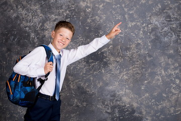 boy in a white shirt and tie with a backpack