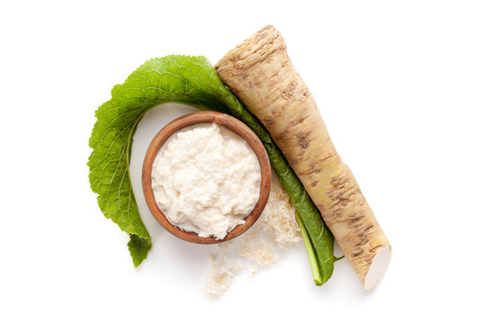 Fresh and grated horseradish in wooden bowl