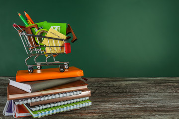 Small shopping cart with different school stationery and notebooks on table against color background