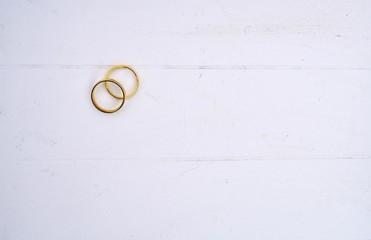 Gold wedding rings on white wood