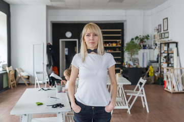 The young blonde woman's portrait with happy emotions in creative studio