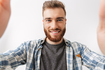 Portrait of a cheerful young bearded man standing