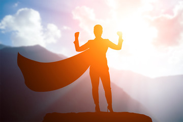 silhouette of a business woman superhero with a cloak standing on top of a mountain in a pose of...