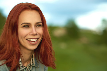 Laughing woman with short red hair posing on green field.