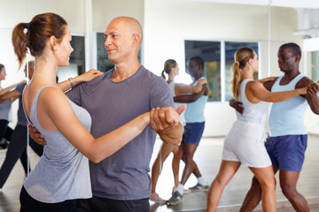 Photo sur Toile Ecole de Yoga Young positive people dancing together slow ballroom dances in pairs