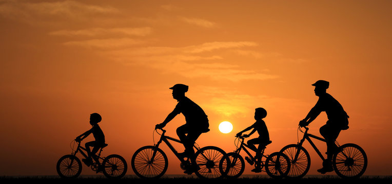 silhouette family  riding bicycle at sunset sky