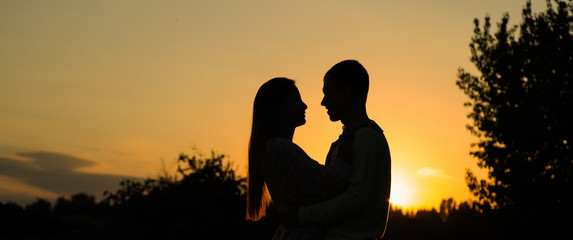 Silhouette couple kissing over sunset background, Profiles of romantic couple looking at each other on background of sunset