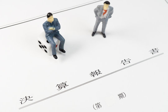 決算報告書と会議する男性