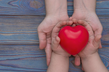 the hands of an adult and a child are held in the red heart, health insurance, family insurance, health day, donation