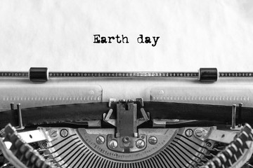 Earth day text is typed on a vintage typewriter with black ink on old paper, close-up