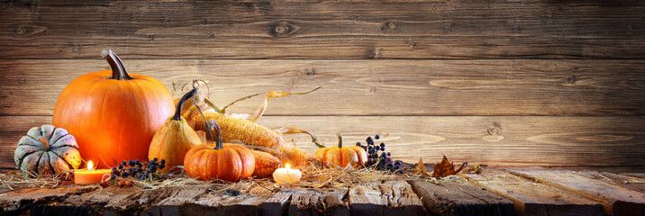 Thanksgiving Background - Pumpkins With Corncob And Candles On Rustic Wooden Table