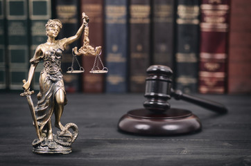Judge Gavel and Lady Justice on a black wooden background.