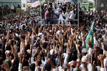 Supporters of the Tehrik-e-Labaik Pakistan Islamist political party raise their hands as they listen to the speech of their leader during a protest march to condemn the cartoon competition by the Netherlands, in Lahore