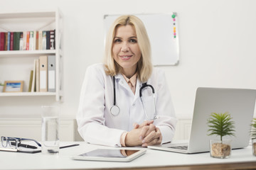 Portrait of female doctor sitting at desktop