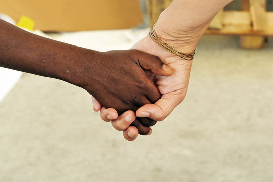 Foster mother. Interracial concept. Black hand and white hand